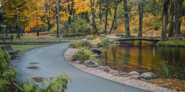 Vista panorâmica. vista do parque outono com um caminho a pé e uma ponte sobre o rio. riga. letônia.