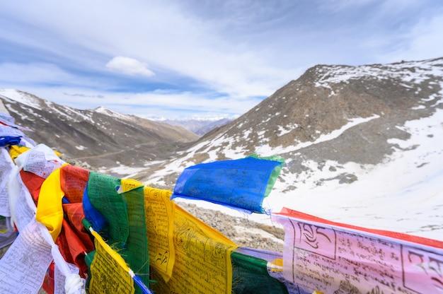 Vista para a montanha de neve com bandeira de oração tibetana na índia