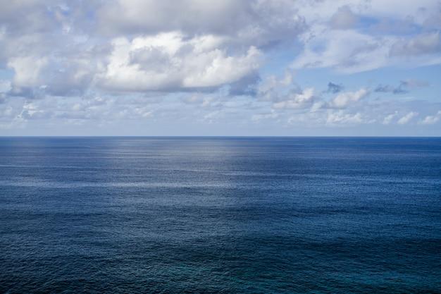 Vista para a noite do oceano atlântico, com horizonte e nuvens brancas