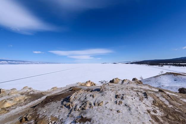 Vista para a praia de sarai do cabo burhan na ilha de olkhon em dia ensolarado de inverno. lago baikal congelado coberto de neve. as nuvens stratus bonitas sobre o gelo surgem em um dia gelado.