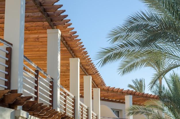 Vista para a varanda do hotel resort egito contra o céu azul e o ramo de palmeira.