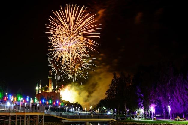 Vista para o céu noturno e lindos fogos de artifício laranja explodindo na cidade