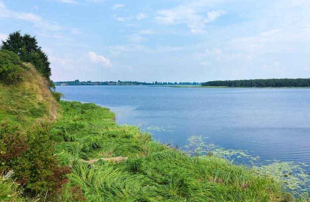 Vista para o lago no verão com um pequeno bosque na margem oposta