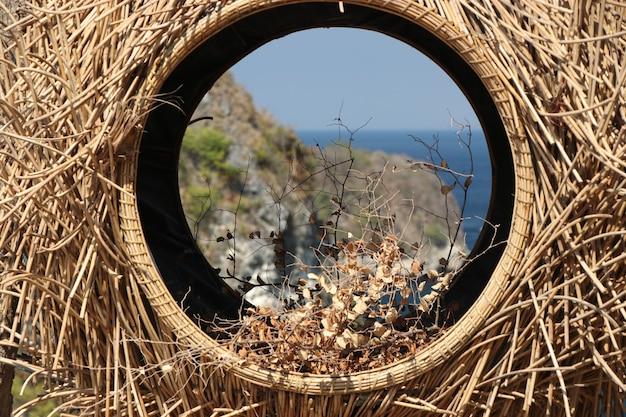 Vista para o mar através de um ninho de pássaro feito de palha na ilha de nusa penida, perto de bali, indonésia, closeup, orientação horizontal