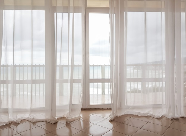 Vista para o mar através de uma cortina transparente em uma enorme janela panorâmica com varanda, interior moderno de apartamentos em um hotel de luxo.