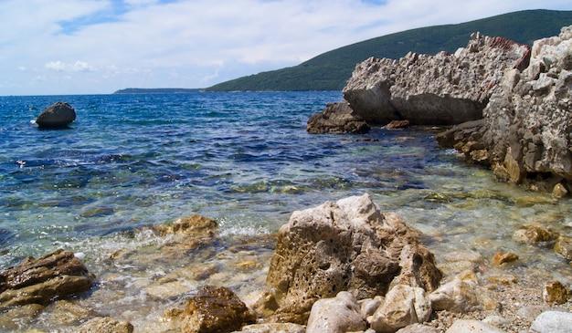 Vista para o mar com pedras e céu nublado, montenegro, cidade de perast