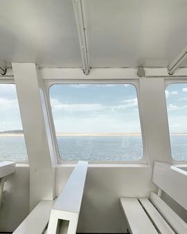 Vista para o mar da janela de um iate com interior branco