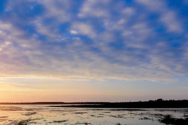 Vista para o rio à noite, nuvens altocumulus.