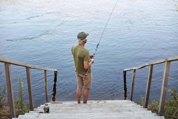 Vista para trás do homem captura peixes enquanto posava nas escadas de madeira, levando ao lago, homem vestindo trajes casuais, apreciando a bela natureza e pesca.