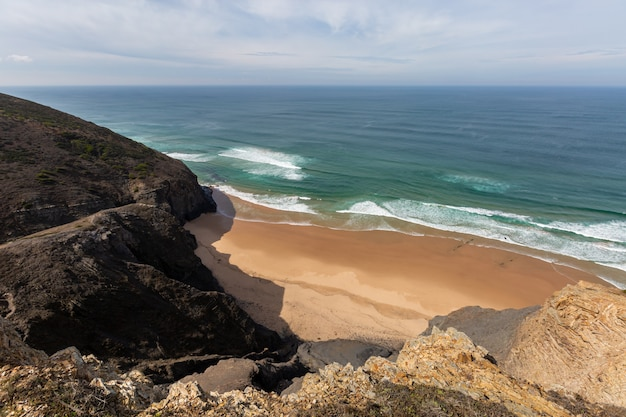 Vista para uma praia rodeada de mar e rochas sob um céu azul em portugal, algarve
