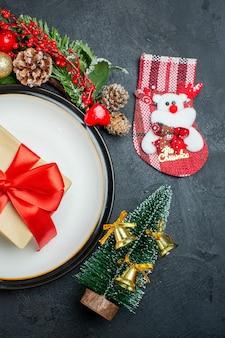 Vista parcial da caixa de presente no prato de jantar árvore de natal ramos de coníferas cone de papai noel chapéu caídas taças de vidro em fundo escuro