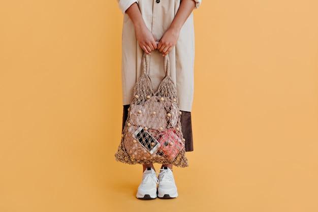 Vista parcial de mulher com bolsa de barbante