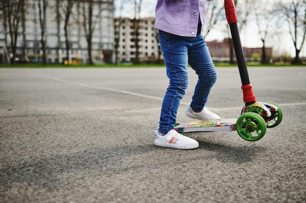 Vista parcial de uma menina andando de scooter ao ar livre contra edifícios desfocados da cidade