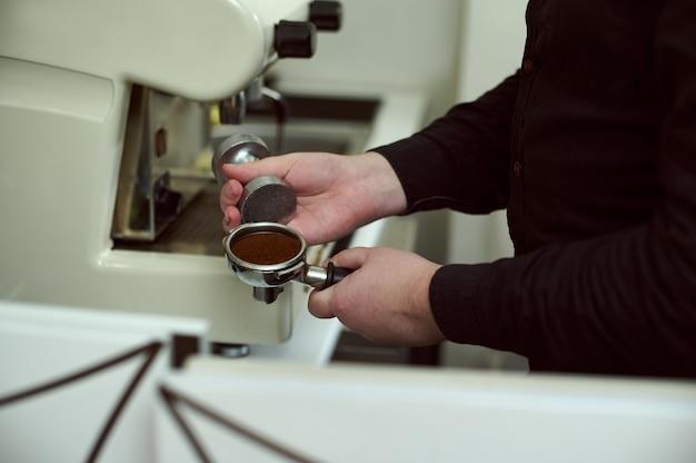 Vista parcial do barista de camisa preta segurando um porta-filtro com café moído e adulterador