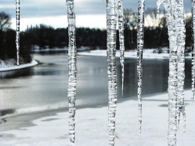 Vista pela janela com pingentes de gelo no rio congelado
