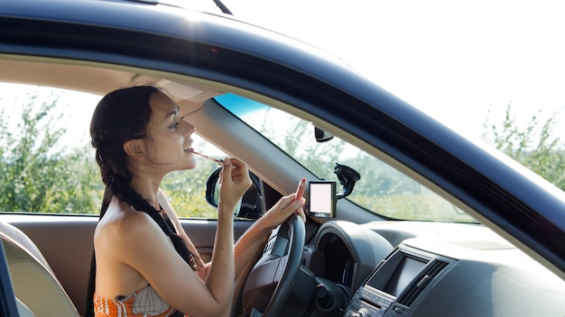 Vista pela janela lateral de uma motorista do sexo feminino aplicando maquiagem usando o espelho retrovisor no carro