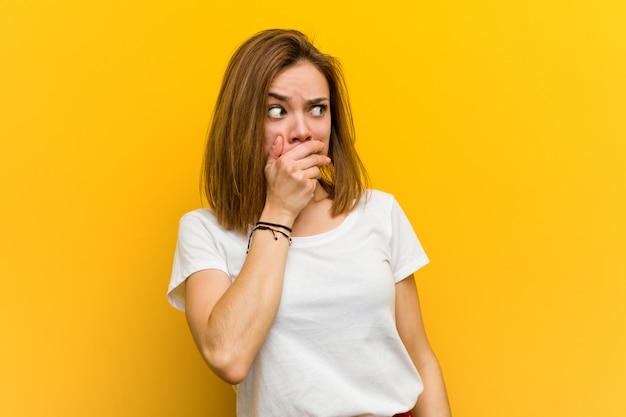 Vista pensativa da mulher caucasiano natural nova a um espaço da cópia que cobre sua boca com a mão.
