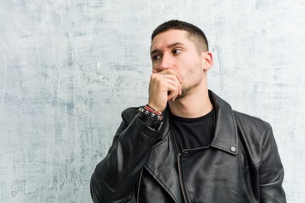 Vista pensativa do homem novo do balancim a uma boca da coberta do espaço da cópia com mão.