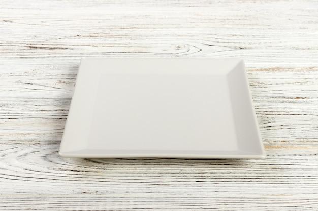 Vista perspectiva, um, quadrado, prato, ligado, a, branca, tabela madeira