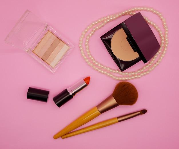 Vista plana, cosméticos de vista superior em fundo rosa