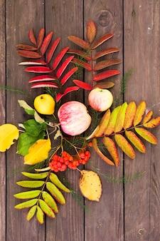 Vista plana das folhas de rowan, pêra e maçã com frutas em uma mesa de madeira no jardim