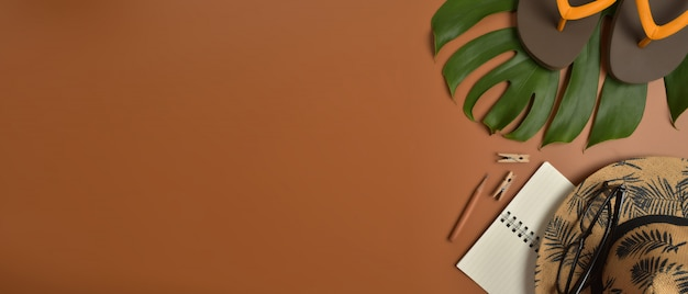 Vista plana, espaço de trabalho de vista superior com óculos, caderno, chapéu, lápis, folha verde, sapatos e xícara de café sobre fundo marrom.