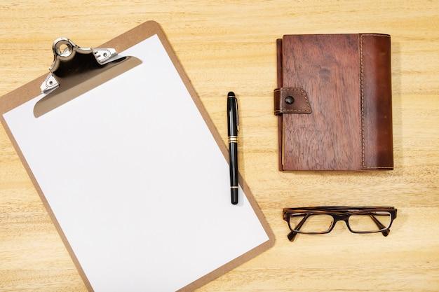 Vista plana leiga, mesa de escritório mesa superior. espaço de trabalho com placa de grampo em branco, caneta, óculos e diário na mesa de madeira