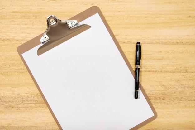 Vista plana leiga, mesa de escritório mesa superior. espaço de trabalho com prancheta em branco e caneta
