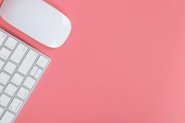 Vista plana leiga, mesa de escritório mesa superior. espaço de trabalho com teclado e mouse em fundo rosa