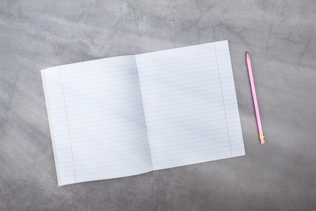 Vista plana leiga, topo, caderno, lápis em um cinza texturizado. raios de luz do lado.
