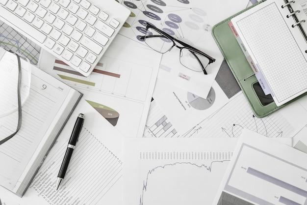 Vista plana leigos da mesa de escritório de lugar de obras com óculos