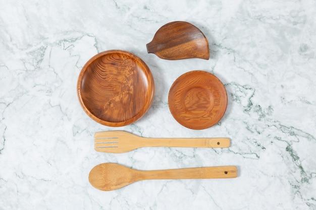 Vista plana leigos de colheres de pau, padrão de disco de madeira na mesa de mármore.
