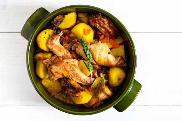 Vista plana superior de carne de coelho assado com legumes e ervas em vaso de cerâmica redondo na superfície da mesa de madeira branca, cópia espaço