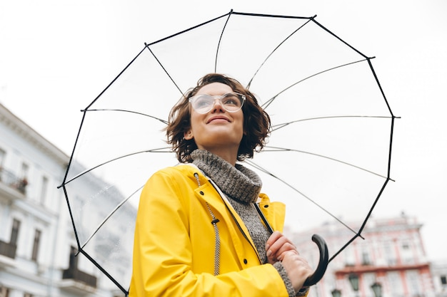 Vista por baixo da mulher positiva na capa de chuva amarela e óculos em pé na rua sob o grande guarda-chuva transparente durante o dia chuvoso cinza
