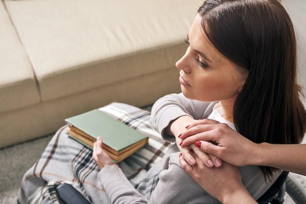 Vista por cima do ombro de um amigo irreconhecível apoiando uma mulher com deficiência sentada com um livro na cadeira de rodas