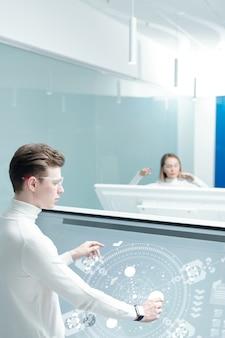 Vista por cima do ombro de um jovem com óculos inteligentes, compondo elementos no esquema usando display interativo em um escritório moderno
