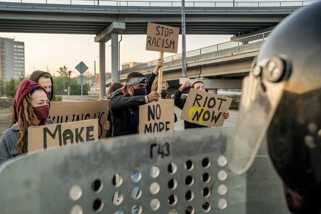 Vista por cima do ombro de um policial irreconhecível com um capacete segurando um escudo antimotim enquanto enfrenta uma multidão que protesta contra o racismo
