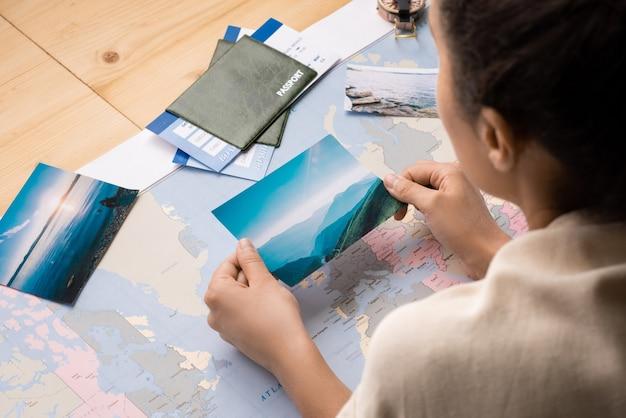 Vista por cima do ombro de uma mulher inclinada sobre a mesa com o mapa-múndi e vendo fotos enquanto sonha em viajar