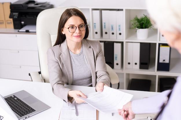 Vista por cima do ombro de uma mulher sênior entregando papéis preenchidos ao consultor do banco para exame