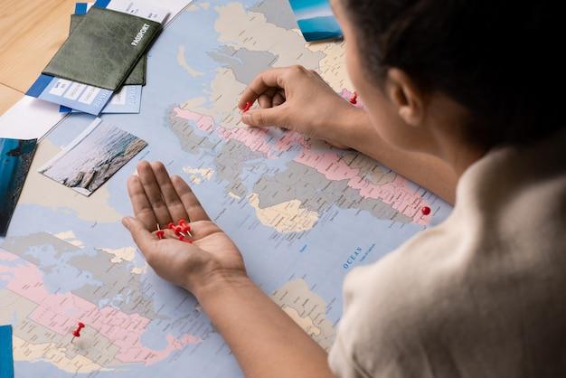 Vista por cima do ombro de uma mulher usando alfinetes vermelhos enquanto marca lugares para viagens no mapa mundial