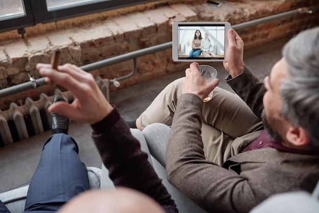 Vista por cima do ombro do empresário com o vidro compartilhando a foto da esposa e da filha no tablet para um amigo na festa