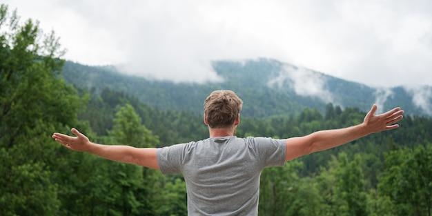 Vista por trás de um jovem de pé na bela natureza verde com os braços bem abertos, curtindo a vida e a abundância.