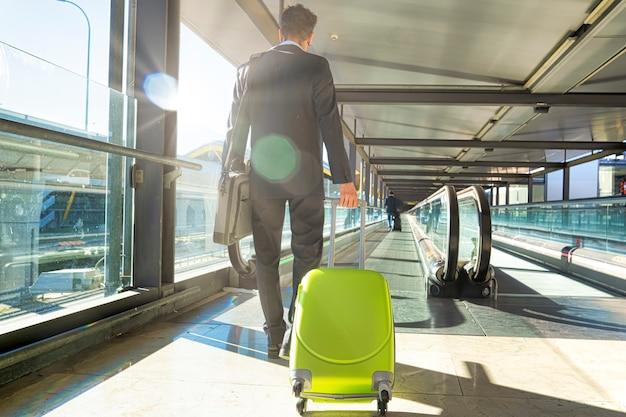 Vista por trás de um jovem empresário vestido de terno viajando de avião com a mala de roda nas escadas rolantes do aeroporto