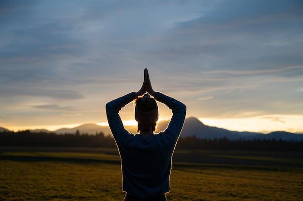 Vista por trás de uma jovem mulher meditando com as mãos juntas acima da cabeça, do lado de fora na bela natureza ao pôr do sol brilhando no céu dramático.