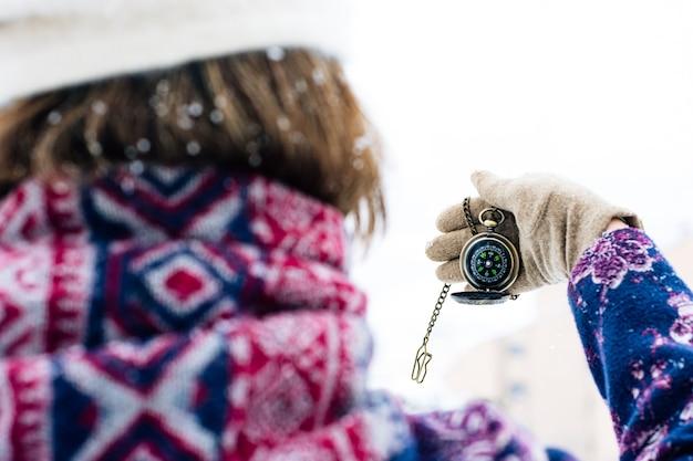 Vista por trás de uma mulher segurando uma bússola no meio de uma tempestade de neve.