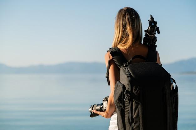 Vista por trás do fotógrafo profissional feminino com bolsa de câmera nas costas