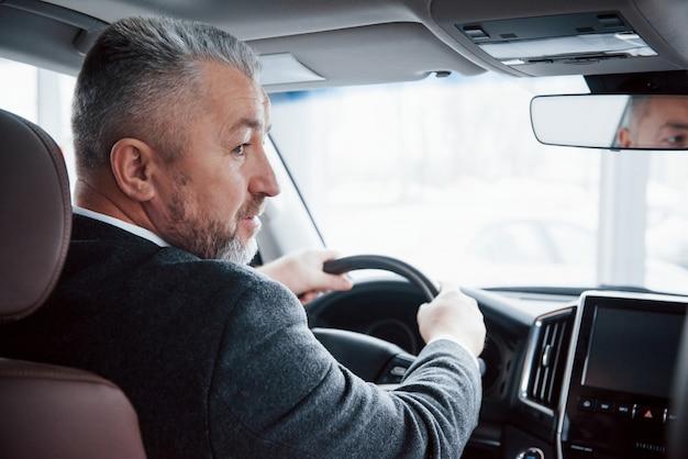 Vista por trás do homem de negócios sênior em roupas oficiais, dirigindo um carro novo e moderno