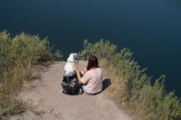 Vista rara da mulher sentar-se com o cão merle pastor australiano na margem do rio, verão. amor e amizade entre humanos e animais. viaje com animais de estimação.