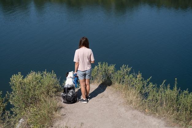 Vista rara de mulher ficar com cão pastor australiano merle azul na margem do rio, verão. amor e amizade entre humanos e animais. viaje com animais de estimação.