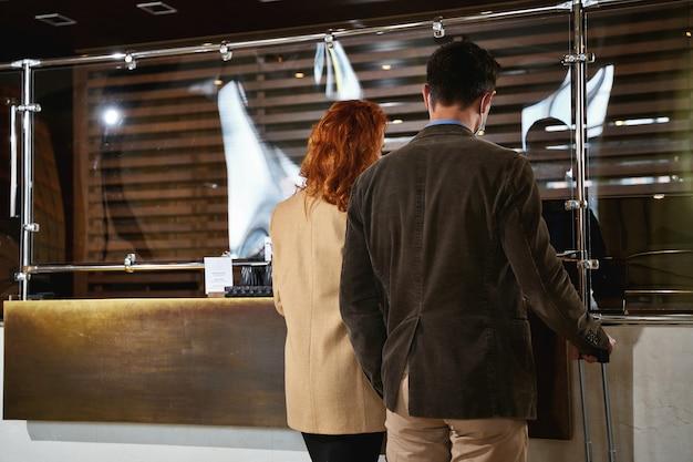 Vista rara de um casal adulto em frente a um escudo de vidro na bancada durante o check-in. banner modelo